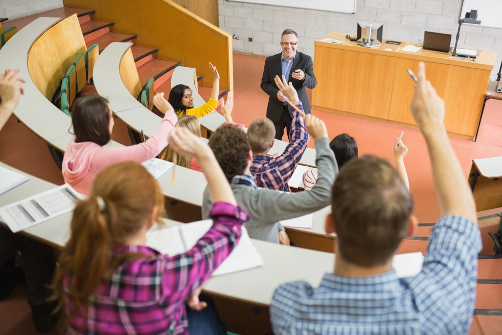 Rear view of students raising hands with a teacher in the college lecture hall.jpeg