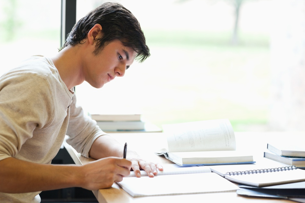 Serious male student writing in a laboratory