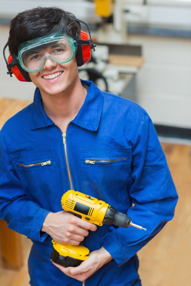 Smiling student standing in a woodwork class and holding a driller.jpeg